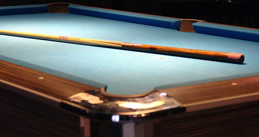 A Billiard table with a wooden cue on it.