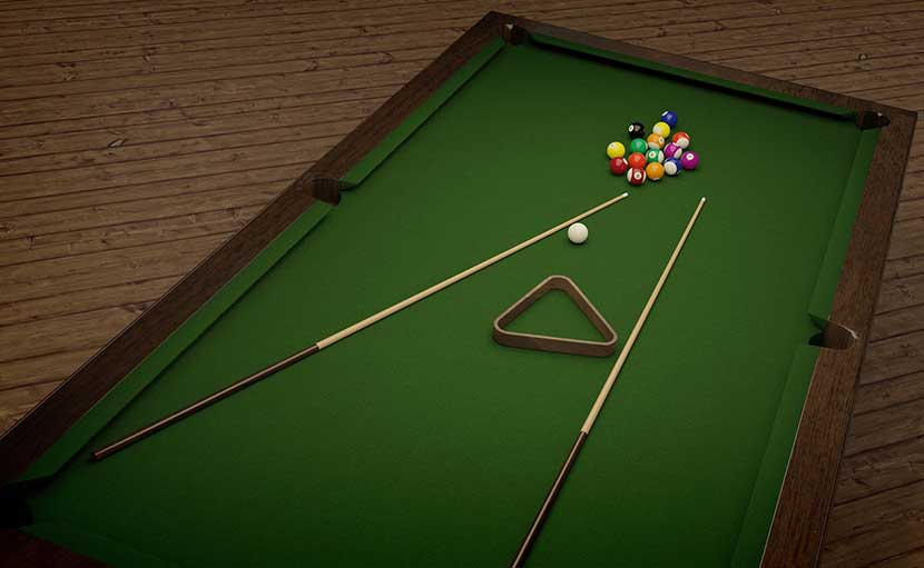 This is a picture of a pool table with two wooden pool cues, balls, and a triangle.